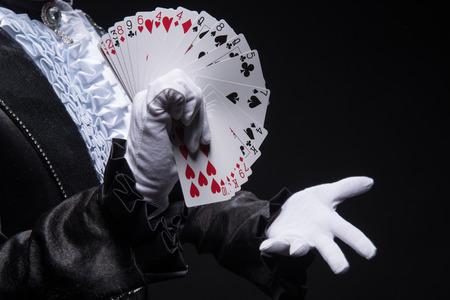 Half-length portrait of  juggler wearing interesting black costume and white shirt showing us his cards  Isolated on black background Reklamní fotografie