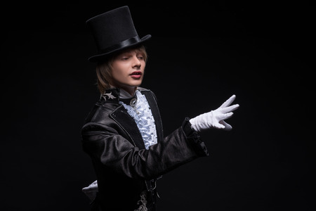 mastery: Half-length portrait of fair-haired matchless juggler wearing interesting black costume white shirt and topper standing aside showing us mastery of his hands  Isolated on black background Stock Photo