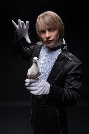 conjuring: Half-length portrait of fair-haired matchless juggler wearing interesting black costume and white shirt conjuring at the white pouter  Isolated on black background Stock Photo