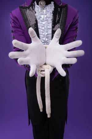 Half-length portrait of juggler wearing splendid violet jacket white shirt and black pants standing with tied hands  Isolated on blue background photo