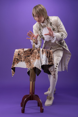 conjuring: Full-length portrait of fair-haired concentrated juggler wearing great white costume standing near the small table conjuring at the burnt candle  Isolated on violet background