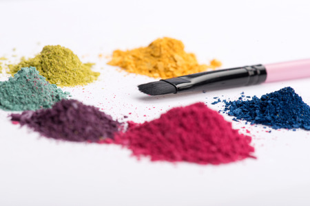 Close-up low angle view of professional make-up brush surrounded by heaps crashed in small pieces eye shadow in pink, blue, yellow, green and purple colours isolated on white background photo