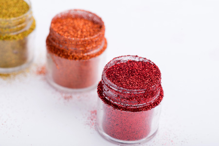 Close-up view of  powder eye shadows  in red, orange and yellow colours isolated on white background with selective focus on red powder eyeshadow  with copy place photo