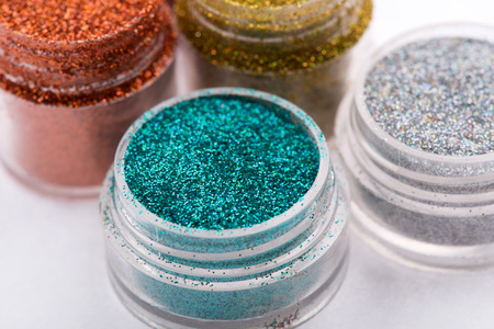 Close-up view of  powder eye shadows  in red, blue,  yellow and silver colours isolated on white background with selective focus on blue powder eyeshadow photo
