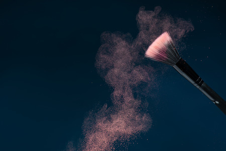 Horizontal close-up photo of professional   black make-up brush with pink powder in motion isolated on blue background with copy place photo