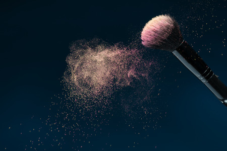 Horizontal close-up photo of professional   black make-up brush with pink powder in motion isolated on blue background with copy place