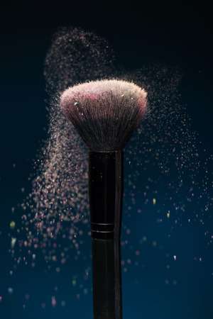 Vertical close-up photo of professional   black make-up brush with pink powder in motion isolated on blue background  photo