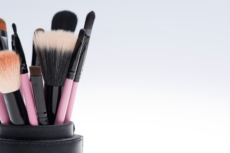 Close-up of Set of professional  different sizes make-up brushes in black tube isolated on white background with copy place