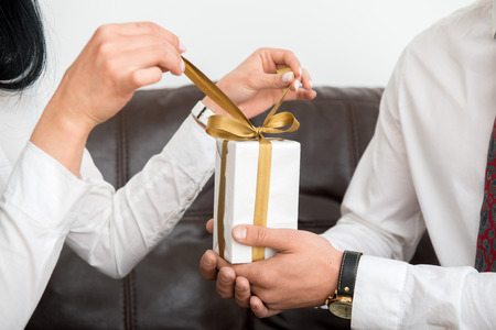 Close-up  view of hands of man giving white gift box, female hands opening gift box in office interior photo