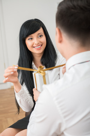 Back view of young businessman giving white gift box to pretty colleague sitting on sofa in office ,woman happy looking at him and opening gift box photo