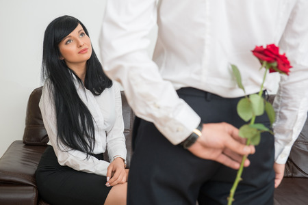 Back view of young businessman  hiding a rose  for his  pretty colleague  sitting on sofa in office and  surprised looking at him photo