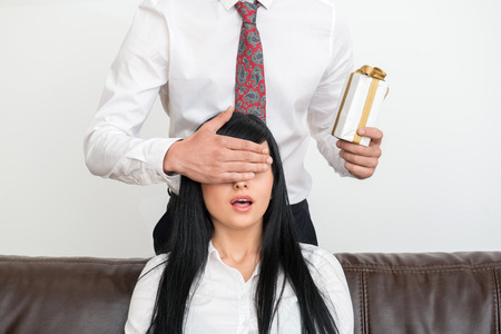 Young businessman standing behind and holding present for pretty and surprised woman sitting on sofa  and closing with his hand  her eyes in office interior photo