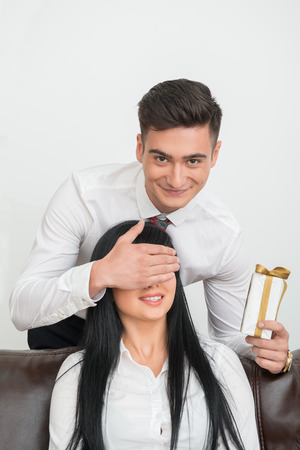Portrait of young  smiling businessman standing behind and closing with his hand eyes of pretty  and happy woman and holding present in white box for her in office interior photo