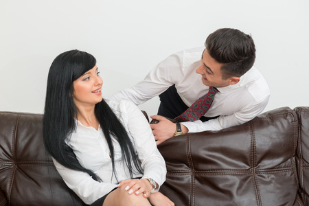 Half-length Portrait of young businessman  and his pretty colleague woman smiling to each other in office interior photo