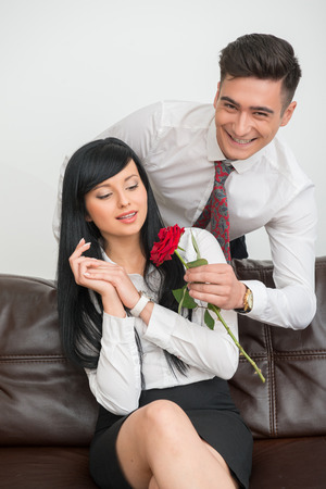 Half-length Portrait of young smiling businessman  standing behind pretty surprised woman colleague  giving her a flower  and looking to the camera photo
