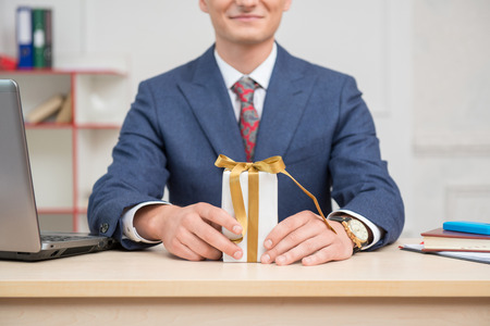 White present box with gold ribbons standing on the table in hands with a clock of young businessman in office surrounded by computer,notebook and mobilephone photo