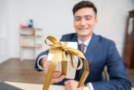 Close-up selective focus on a gift box in hands of young businessman in office working on his computer,showing a box to the camera photo
