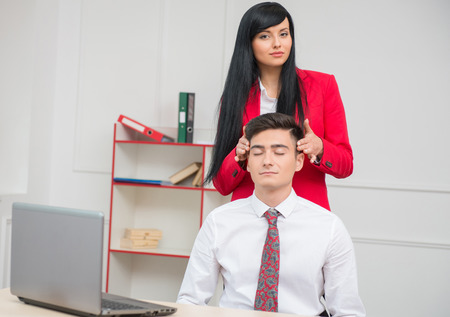 Portrait of young business woman looking at the camera and doing head massage to her colleague with closed eyes sitting at the desk in office with copy space, relationship at work concept