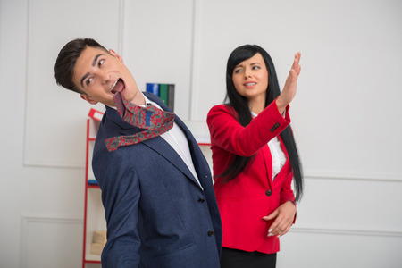Portrait of young business woman in red jacket  giving a slap in the face to her flirting colleague in office, relationship at work concept photo