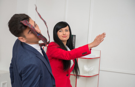 Portrait of young crying  business woman in red jacket  giving a slap in the face to her flirting colleague in office, relationship at work concept photo