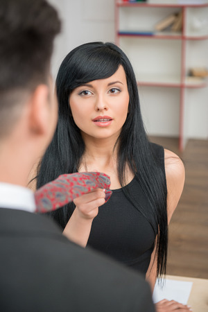 Portrait of young charming businesswoman flirting and pulling her colleague by the tie, looking with love at him in office  photo