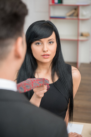 Portrait of young charming businesswoman flirting and pulling her colleague by the tie in office, looking at the camera photo