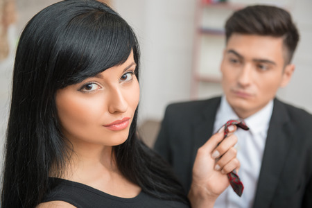 Close-up Portrait of young charming businesswoman flirting and pulling her colleague by the tie in office, looking at the camera photo