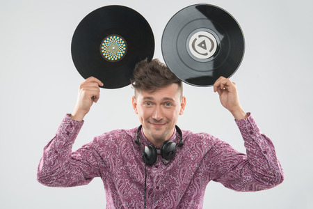 mickey: Closeup portrait of excited young DJ with stylish haircut, bow tie having fun with vinyl record showing Mickey Mouse ears isolated on white background Stock Photo