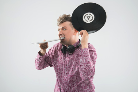 sound bite: Closeup portrait of excited young DJ with stylish haircut, bow tie having fun with vinyl record biting it isolated on white background Stock Photo