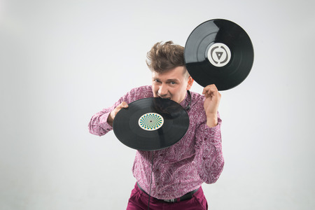 sound bite: Top view closeup portrait of excited young DJ with stylish haircut, bow tie having fun with vinyl record biting it isolated on white background