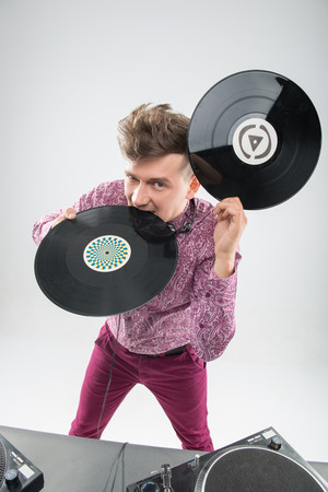 sound bite: Top view half-length portrait of excited young DJ with stylish haircut, bow tie having fun with vinyl record biting it isolated on white background