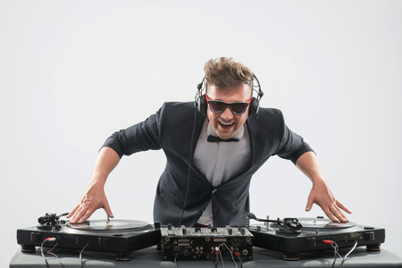 Half-length portrait of stylish emotional handsome DJ in tuxedo and sunglasses spinning and mixing music on turntable isolated on white background