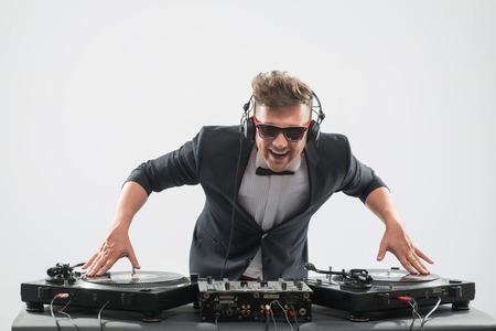 fiestas electronicas: Retrato de medio cuerpo de estilo DJ guapo emocional en smoking y gafas de sol girando y mezclar música en el tocadiscos aislados en fondo blanco