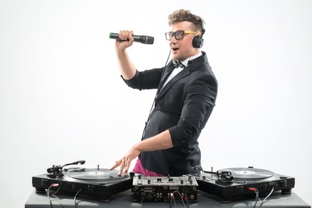 Half-length portrait of stylish emotional DJ in tuxedo spinning and dancing by the turntable with microphone isolated on white background, side view