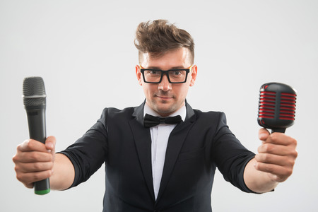 mc: Half-length portrait of stylish emotional MC in tuxedo posing with two different microphones isolated on white background