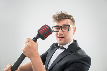 mc: Close-up sideview portrait of stylish emotional MC in tuxedo with haircut and sunglasses sinning in retro microphones isolated on white background
