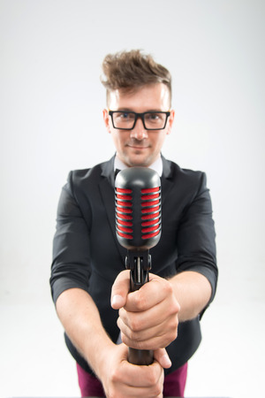 mc: Half length portrait of stylish emotional MC in tuxedo with haircut and sunglasses posing with retro microphones isolated on white background