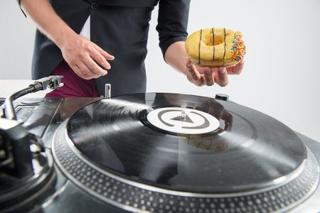 Closeup portrait of DJ placing donut on vinyl record on turntable, stylish look in tuxedo, isolated on white, concept of food at work with experiment photo