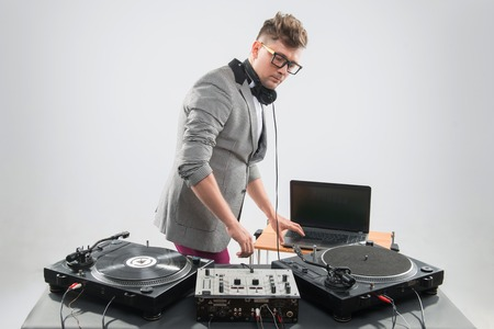 DJ playing music with stylish haircut and glasses and headphones with grey jacket at work spinning on mixer looking down while standing isolated on white background Stock Photo