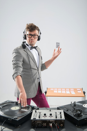 turning table: DJ playing music with stylish haircut and glasses and headphones with grey jacket at work spinning on mixer looking down while standing isolated on white background Stock Photo