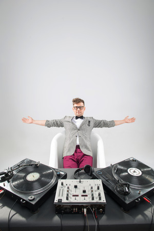 turning table: Top view of confident young DJ with stylish haircut and glasses and headphones in the bath near on mixer isolated on white background