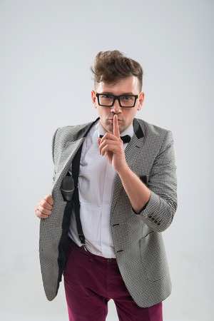 mc: Half length portrait of stylish emotional MC in jacket with haircut and glasses showing sign silence isolated on white background