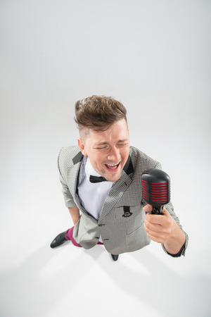 mc: Top view portrait of stylish emotional MC in jacket with haircut posing with retro microphones isolated on white background