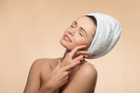 Closeup Portrait of girl in spa with clean and  fresh skin, with closed eyes touching her face, with a towel on her head photo