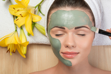 Close-up portrait of beautiful girl with closed eyes  with a towel on her head applying facial clay mask and beauty treatments lying on a table in spa near yellow flower Archivio Fotografico