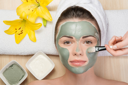 Close-up portrait of beautiful girl looking at the camera with a towel on her head applying facial clay mask and beauty treatments lying on a table in spa near yellow flower and two plates