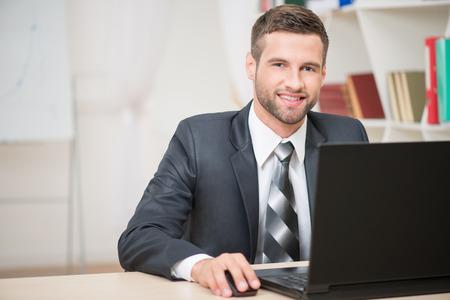 confidence: Horizontal retrato de apuesto hombre de negocios sentado en la mesa de trabajo con ordenador port�til mirando a la c�mara y sonriendo feliz en el fondo de la oficina