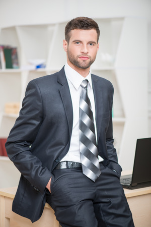 waistup: Waist-up portrait of handsome confident businessman sitting on his table in office looking at the camera and keeps his hands in pockets Stock Photo
