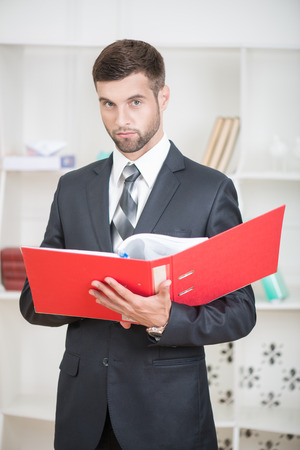 proffesional: Waist-up portrait of handsome confident businessman standing in office with a red folder in his hands and looking at the camera with serious face