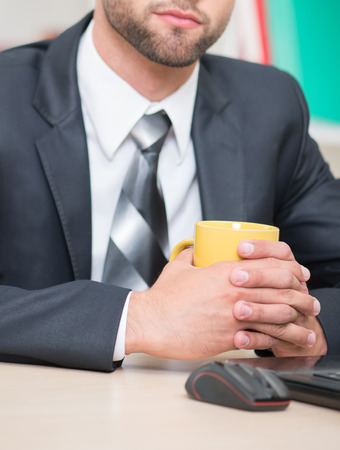 coffeebreak: Close-up portrait of handsome businessman sitting at the table in office enjoying the coffee-break drinking yellow cup of tea and seriously looking at the camera, with copy place